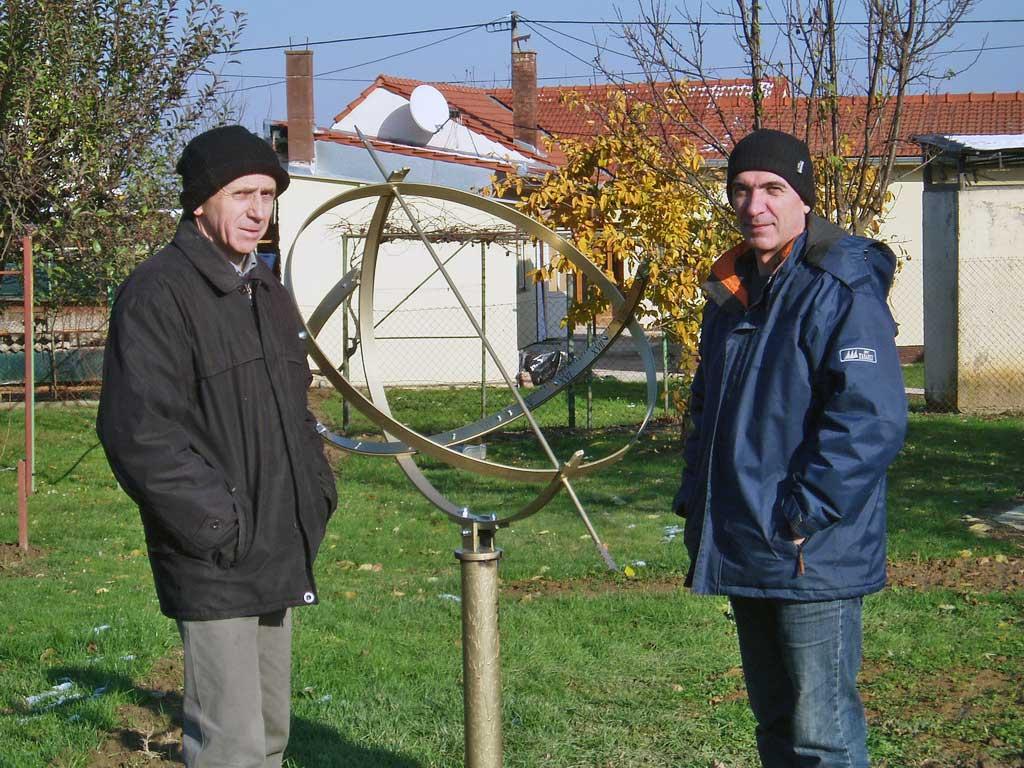 Zlatko i Zoran poziraju, zadovoljni svojim poslom. Između njih je sunčani sat zvjezdarnice Apollo.